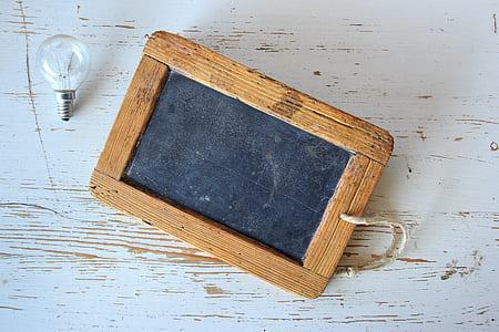 rectangular brown wooden framed board and incandescent bulb