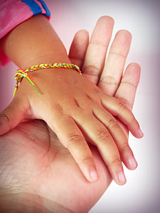 person's hand holding child's hand