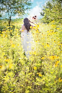 woman wearing white dress on bed of yellow flowers