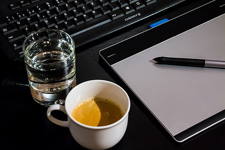 flat lay photograph of clear drinking glass, white ceramic cup, and Wacom Intuos graphics tablet
