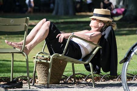woman sitting on gray steel armchair