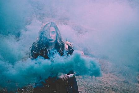 woman with black jacket holding bar-releasing-smoke