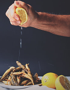 person squeezing lemon on fried fishes