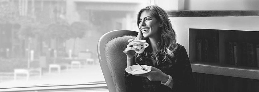 grayscale photo of woman holding saucer and teacup