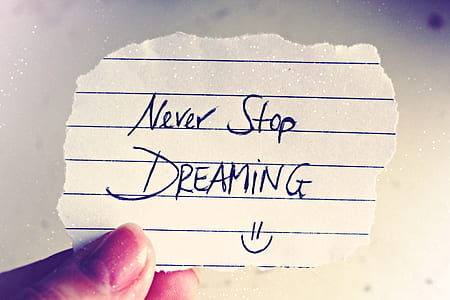 person holding crop paper with Never Stop Dreaming note