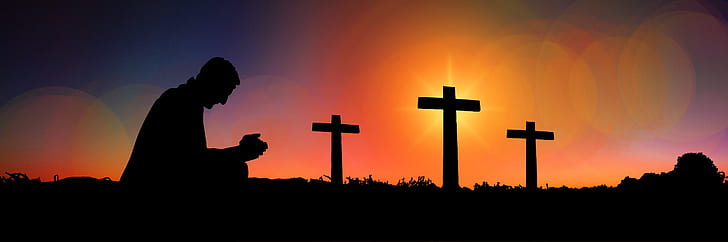 silhouette of man praying with three cross in background