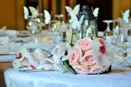 pink rose bouquet beside white orchids on table