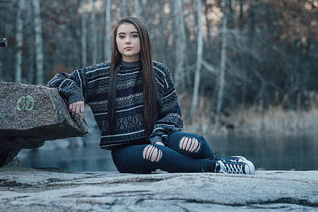 woman leaning on rock