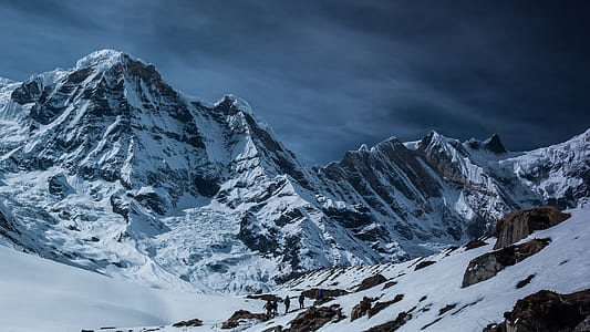 snow capped mountain under grey clouds