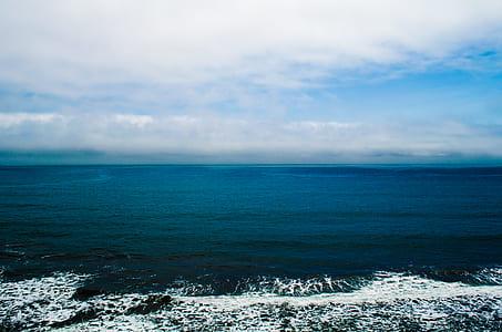 ocean under white clouds