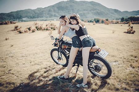 two women riding motorcycle near mountain during daytime