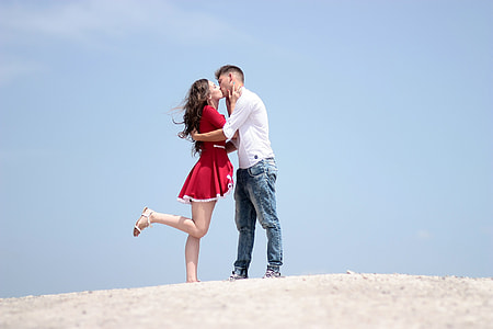 man and woman kissing while standing on white surface during daytime