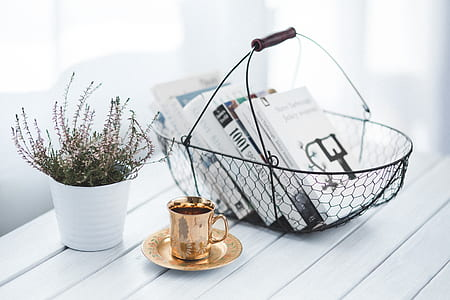 books on metal basket above wooden table