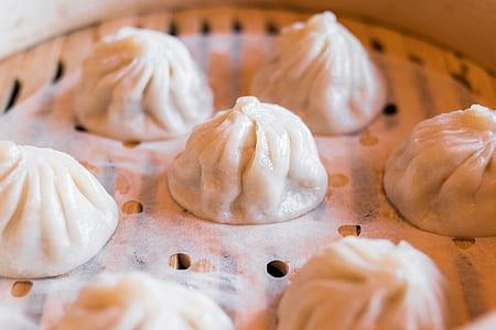 dumplings on brown wooden steamer