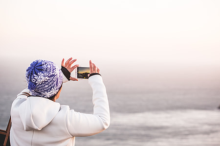Woman in Winter Hat Taking a Picture of Endless Ocean