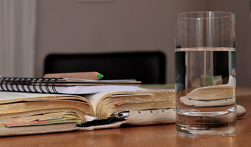 water in clear drinking glass and title book on table