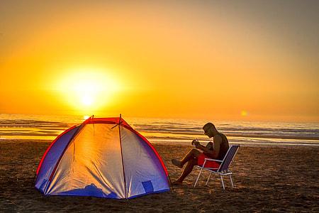 man sitting on white chair near blue and orange dome tent near sea