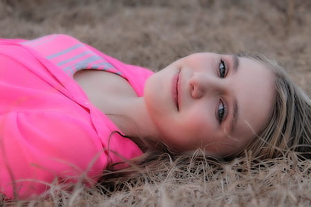 woman wearing pink shirt and lying on brown grassy land