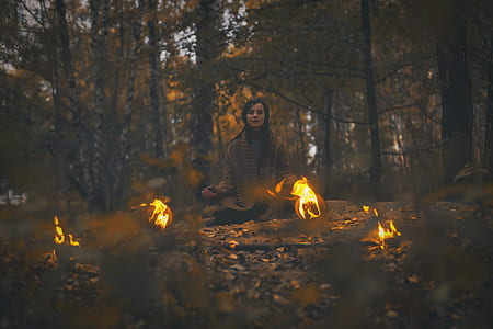 woman wearing brown cardigan sitting in forest surrounded with fireballs