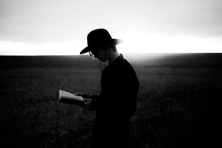 grayscale photography of a person in black dress shirt wearing black hat reading a book
