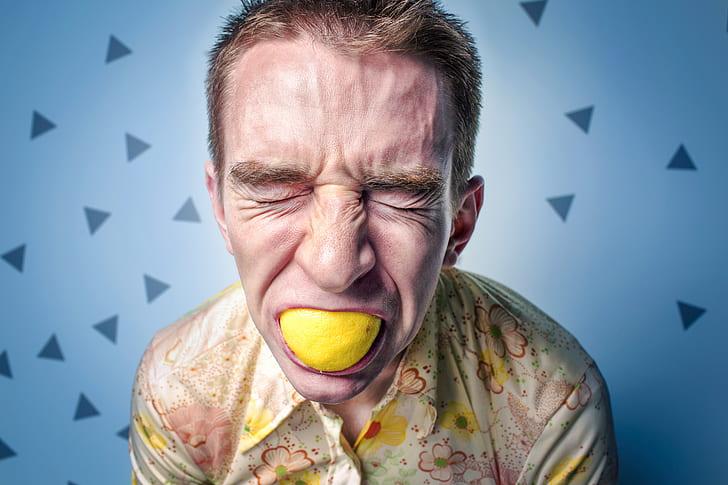 close up photography man eating lemon