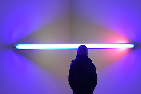 A man stands by abstract lights