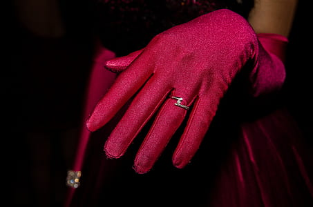person wearing red gloves and silver-colored ring