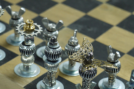 silver-colored gear chess pieces on beige and black board