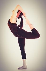 woman in black racerback shirt and black leggings doing yoga