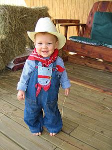 closeup photo of toddler in blue denim jumper pants