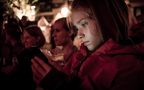 woman in red jacket holding smartphone
