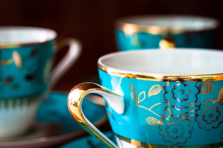selective focus photography of gold and blue floral mug and saucer