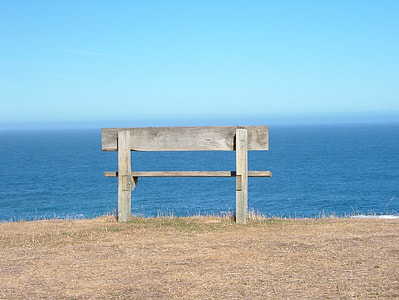 gray wooden bench near body of water