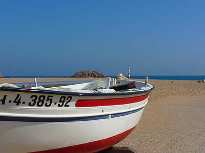 white, red, and blue boat at seashore during daytime