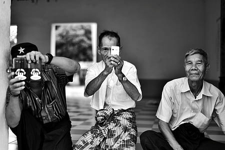 grayscale photo of three men sitting