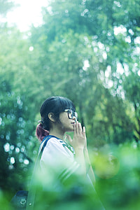 shallow focus photography of black haired girl wearing eyeglasses surrounded by green trees