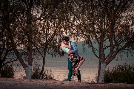 couple kissing near trees during daytime