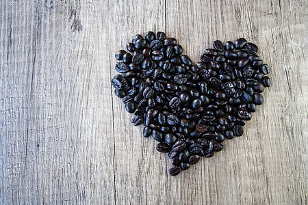 heart-shaped black coffee beans on brown wooden surface