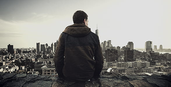 person sitting at the edge overlooking the city