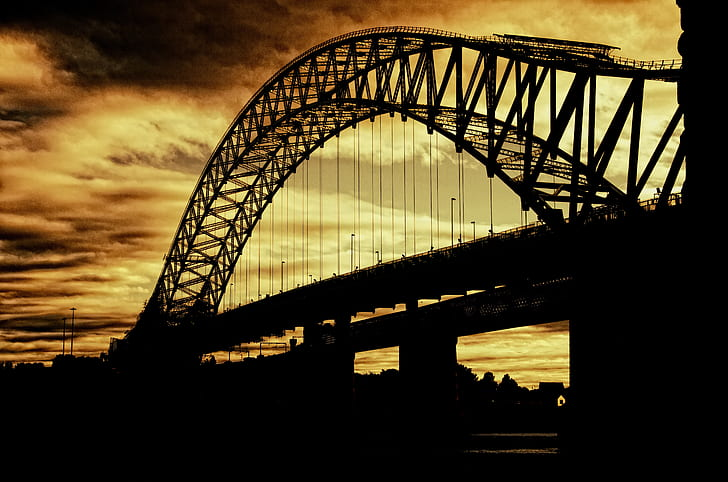 silhouette of metal bridge under yellow sky during twilight