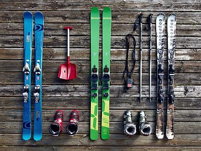 three pairs of snow skis with bindings and ski poles