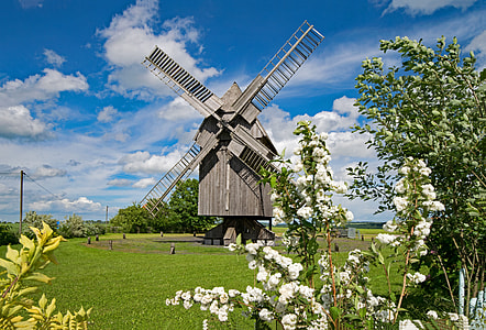 brown wooden windmill in the middle of green grass field under cloudy blue sky during daytime