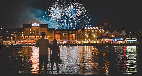 man and woman standing near body of water watching fireworks