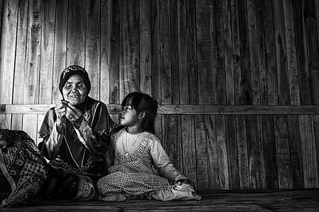 grayscale photo of a woman and child sitting in a corner of a wooden house