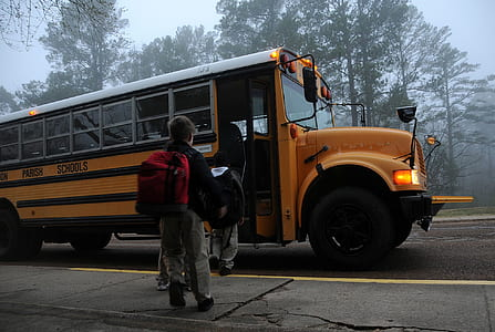 boy carrying black backpack going through yellow school bus