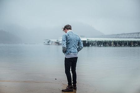man wearing blue denim jacket standing on beach under heavy clouds