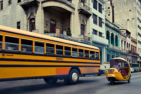 Retro street photo of a public bus and coco taxi, shot taken in Havana, Cuba