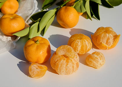 orange fruits on white surface