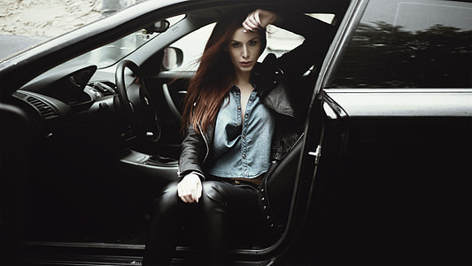 woman in black jacket sitting inside car