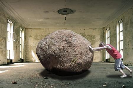 man in red tank top pushing brown stone